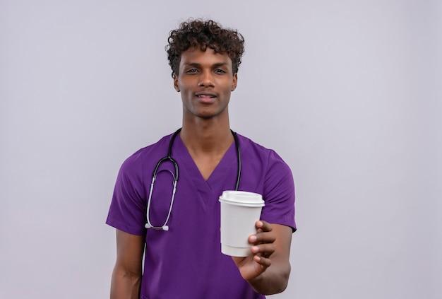 Een zelfverzekerde jonge knappe donkere arts met krullend haar in violet uniform met een stethoscoop die papieren kopje koffie toont