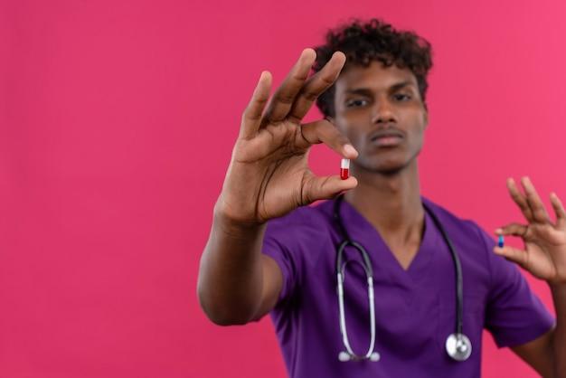 Een zelfverzekerde jonge knappe donkere arts met krullend haar in violet uniform met een stethoscoop die pillen bekijkt