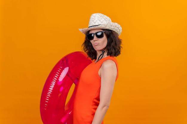 Een zelfverzekerde jonge vrouw met kort haar in een oranje overhemd met een zonnehoed en een zonnebril met roze opblaasbare ring