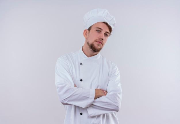 Een zelfverzekerde knappe jonge bebaarde chef-kok man gekleed in een wit fornuis uniform en hoed hand in hand gevouwen terwijl hij op een witte muur kijkt
