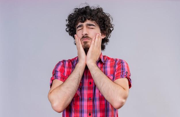 Een zelfverzekerde knappe man met krullend haar in een geruit overhemd die de hand op het gezicht houdt