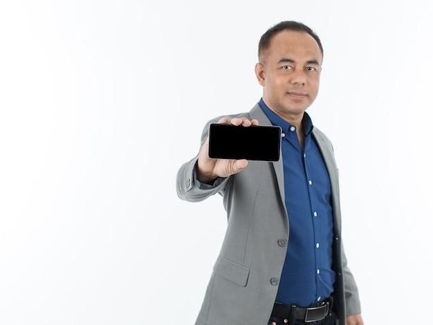 Een zelfverzekerde senior aziatische man in een blauw zakelijk casual shirt met een grijze jas die staat en een smartphone met een leeg scherm op een witte achtergrond toont. selectieve focus op telefoon.