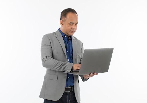 Een zelfverzekerde senior aziatische man van middelbare leeftijd in een blauw zakelijk casual shirt met een grijze jas die de laptopcomputer vasthoudt. isoleer op witte achtergrond.