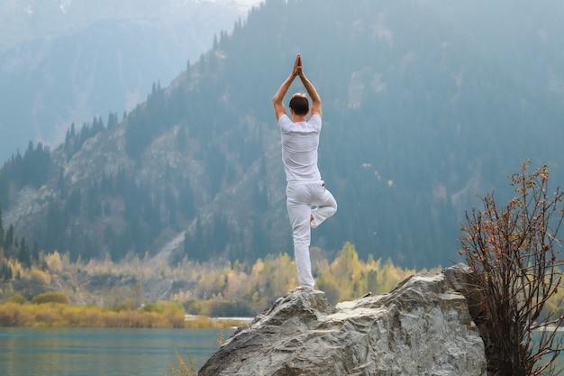Een zen-man in het wit beoefent yoga in de natuur. stel vrikshasana of boomhouding.