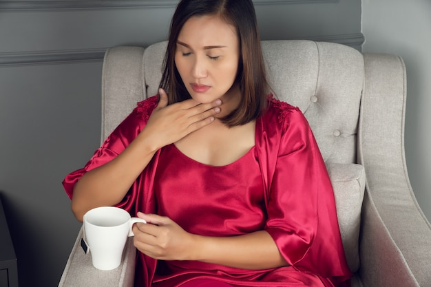Een zere keel is een pijn, krasserigheid of irritatie, aziatische vrouwen in rode zijden nachtkleding met zure reflux 's nachts