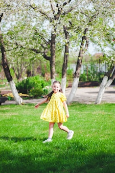 Een zesjarig gelukkig meisje rent op een groen grasveld in het park en heeft een leuke gezinsactiviteit op de ...