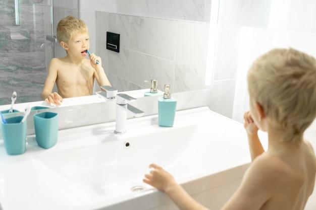 Een zesjarige jongen poetst 's ochtends zijn tanden in het bad voor de spiegel, hygiëne in de ochtend