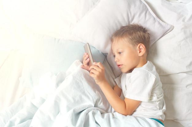 Een zesjarige jongen rust liggend in bed en houdt een smartphone in zijn handen. een kind met een gadget thuis.