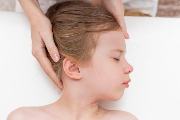 Een zevenjarig meisje op een afspraak met een osteopaat. pediatrische osteopathie. hoofdpijn bij schoolgaande kinderen. correctie van de schedel, wervelkolom.