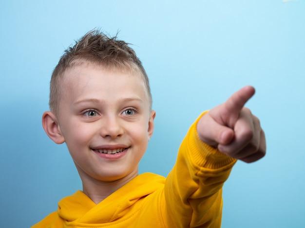 Een zevenjarige jongen poseert voor de camera en toont verschillende emoties, verrassing, vreugde. tiener wijst vinger naar camera