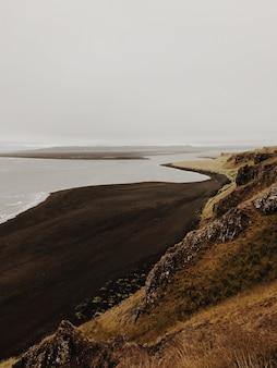 Een zicht op een zwart zandstrand