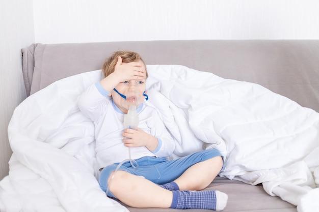 Een ziek kind met een inhalator behandelt thuis de keel en meet met zijn hand de temperatuur, het concept van gezondheid en inhalatiebehandeling