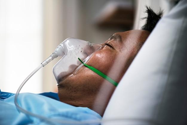 Een zieke aziatische man in een ziekenhuis
