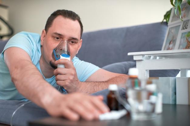 Een zieke man ademt door een inhalatormasker. liggend op de bank en trekt zijn hand naar de remedie