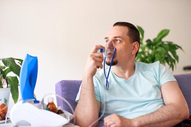 Een zieke man ademt door een inhalatormasker