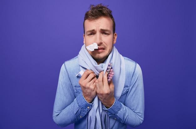 Een zieke man met pillen en een inhalator in handen