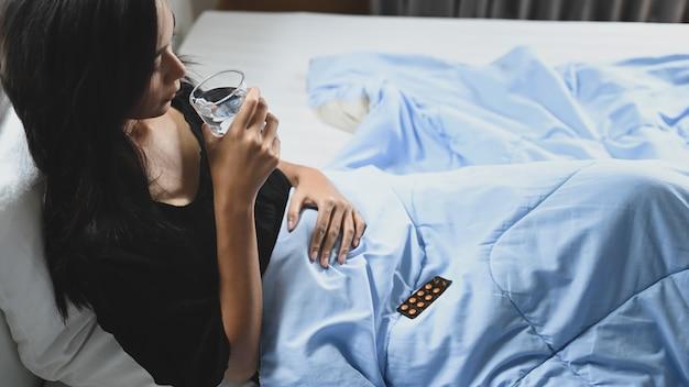 Een zieke vrouw houdt een glas water vast en drinkt een pil bij het bed.