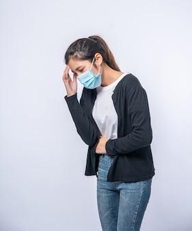 Een zieke vrouw met hoofdpijn droeg een masker en legde een hand op haar hoofd.