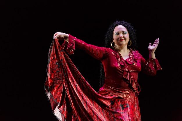 Een zigeunervrouw met zwart krullend haar danst in een rode jurk op een zwarte achtergrond. horizontale foto