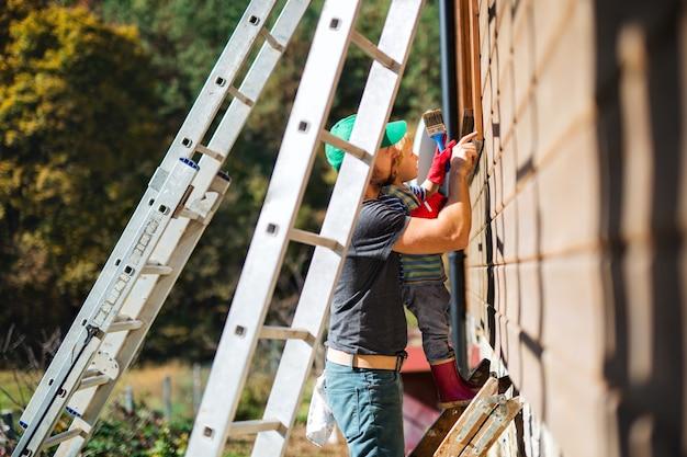 Een zijaanzicht van vader en peuterjongen buiten in de zomer, houten huis schilderend.