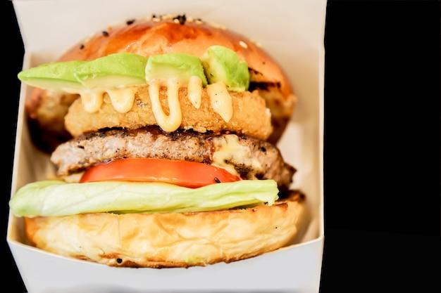 Een zijaanzichthamburger die zijn lagen in een witte doos en een zwarte achtergrond toont