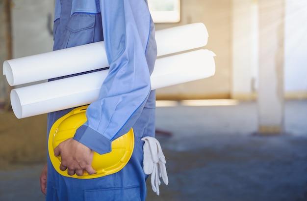 Een zijfoto van een bouwingenieur die een blauwdruk en een gele veiligheidshelm vasthoudt.