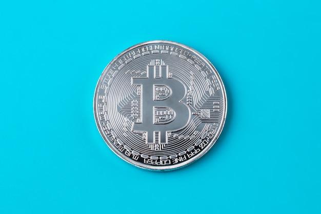 Een zilveren bitcoin op blauwe achtergrond. e-commerce, cryptocurrency. blockchain, internationale mijnbouw.