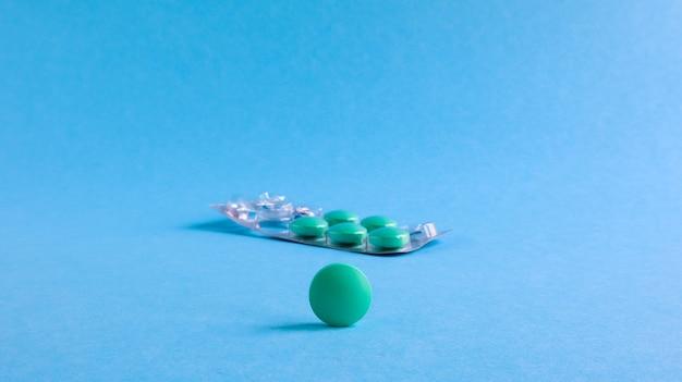 Een zilveren blister met ronde groene pillen en een ronde tablet opzij op een blauwe achtergrond. er ontbreekt één tablet uit de verpakking. conceptuele medicatie. kopieer ruimte voor uw tekst of logo.