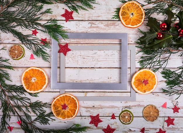 Een zilveren frame met kopie ruimte voor tekst in kerstdecor met kerstboom, droge sinaasappel over oude tafel