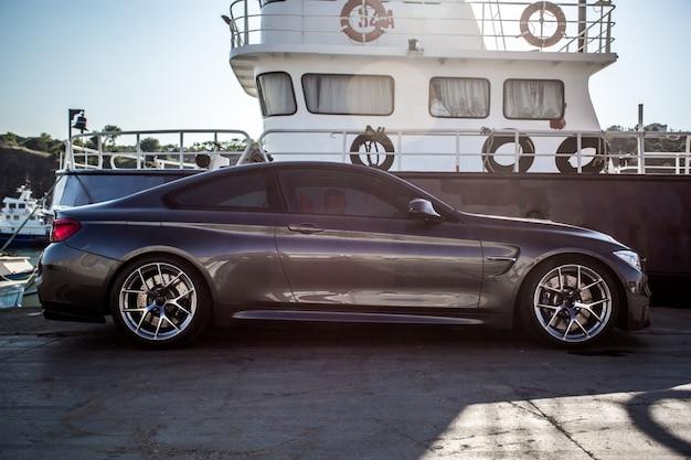 Een zilveren luxe sedan geparkeerd in de haven.
