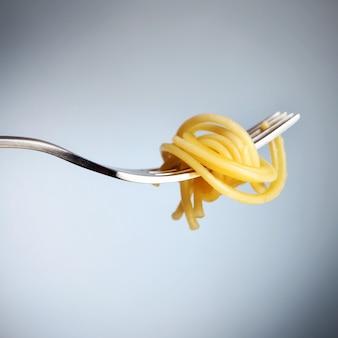 Een zilveren vork met spaghettinoedel over grijze achtergrond
