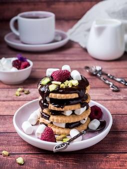 Een zoet dessert van chocoladekoekje, frambozenheemst en een kop van koffie op donkere achtergrond