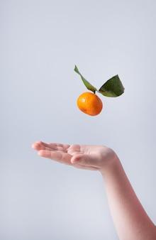 Een zoete en sappige mandarijn wordt door een kinderhand op een grijze achtergrond gegooid. vooraanzicht