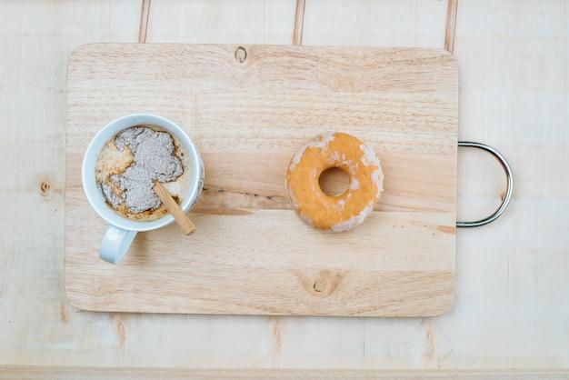 Een zoete kop koffie geplaatst op een houten bord samen met een donut.