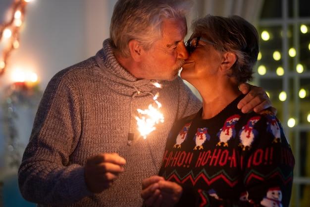 Een zoete kus tussen een senior echtpaar van vrouw en man die kerstmis met vonken vieren. lichtjes en kerstboom op de achtergrond