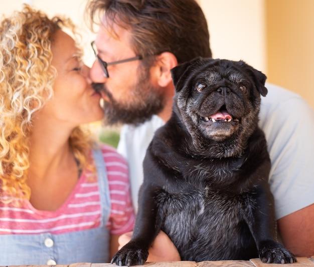 Een zoete kus tussen vrouw en man die hun oude zwarte mopshond omhelzen buiten op terras