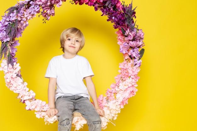 Een zoete schattige schattig aanbiddelijk blonde jongen in witte t-shirt zittend op de bloem gemaakt staan op het gele bureau