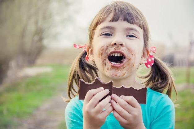 Een zoetekauw kind eet chocolade. selectieve aandacht.