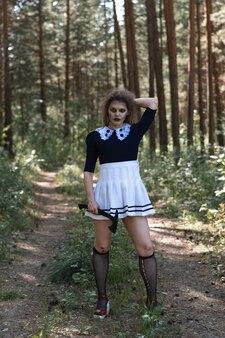 Een zombiemeisje met een bijl in haar handen in een somber bos. halloweenkostuum