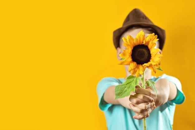 Een zomerjongen in een licht t-shirt met een gele zonnebloem bedekt zijn gezicht