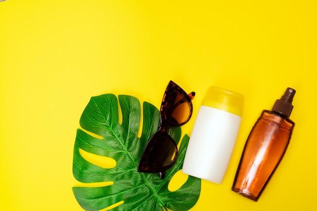 Een zonnebrandcrème, zonnebril op gele tafel