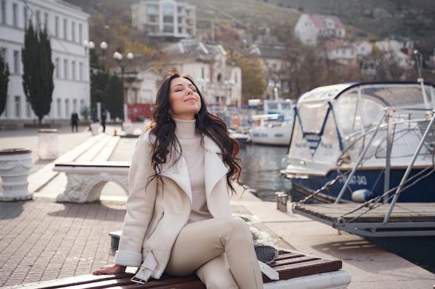 Een zorgeloze blanke vrouw in beige kleding genietend van het uitzicht op de zee op een warme, winderige dag. dame geniet van een mooie winterdag en ademt de zeelucht in