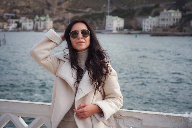 Een zorgeloze blanke vrouw in beige kleding genietend van het uitzicht op de zee op een warme, winderige dag. een vrouw met een stijlvolle zonnebril die geniet van een mooie winterdag en de zeelucht inademt