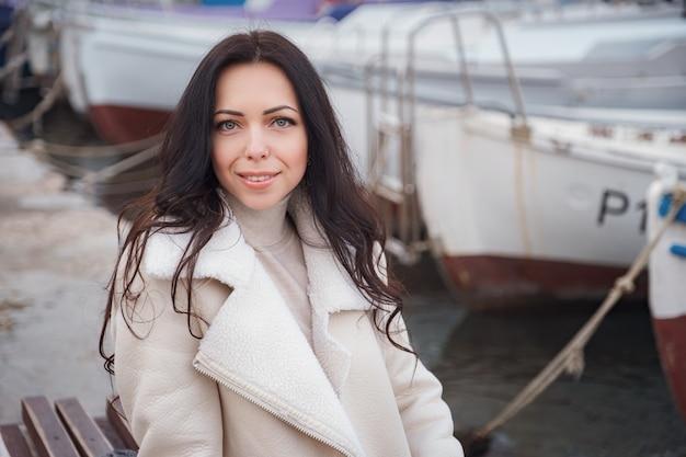 Een zorgeloze blanke vrouw in beige kleding genietend van het uitzicht op de zee op een warme, winderige dag. portret voor een zeebaai met boten op de pier