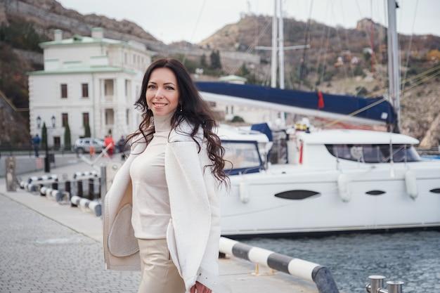 Een zorgeloze blanke vrouw in beige kleding genietend van het uitzicht op de zee op een warme, winderige dag. reis naar zee, reizen, vakantieconcept