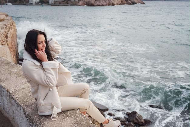 Een zorgeloze blanke vrouw in beige kleding genietend van het uitzicht op de zee op een warme, winderige dag.