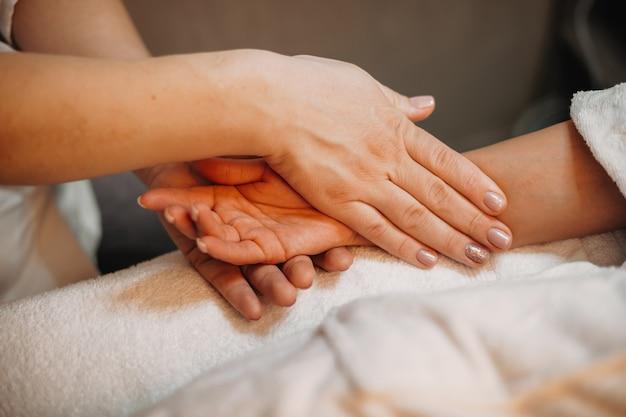 Een zorgvuldige masseur masseert de hand van de cliënt voordat de volgende procedure wordt gestart