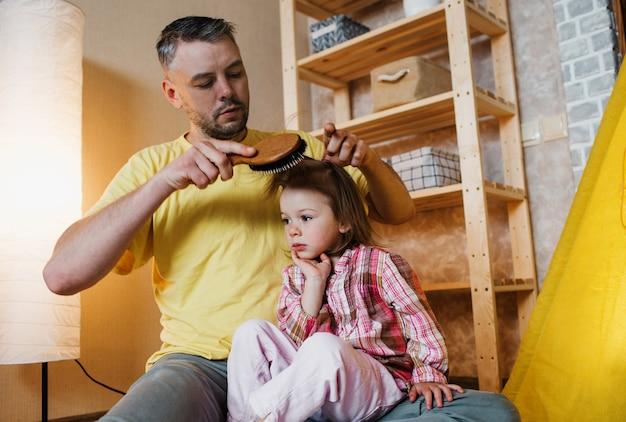 Een zorgzame vader in een geel t-shirt kamt thuis het haar van zijn dochtertje terwijl hij op de grond zit. voor uw kind zorgen.