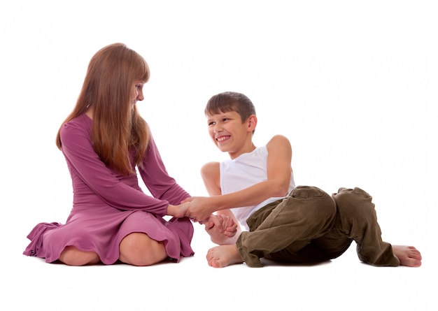 Een zus en een broer spelen samen een spel terwijl ze naast elkaar op de grond zitten.