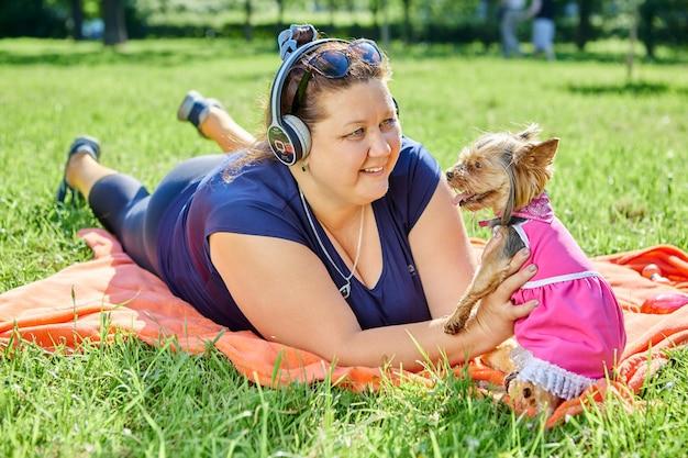 Een zwaarlijvige vrouw ligt op gras met haar buik naar beneden en glimlacht terwijl ze naar de yorkshire terrier kijkt